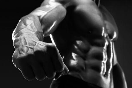 vasos sanguineos: Culturista muscular hermoso muestra su pu�o y la vena, los vasos sangu�neos. Estudio tirado en el fondo oscuro. Foto de archivo