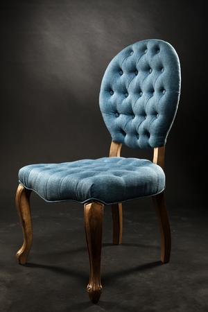 blue velvet: Antique blue velvet chair near a dark room. Old vintage furniture.