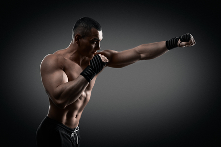 masculine: Fighter boxer standing staring strong on black background. Young masculine caucasian male athlete.