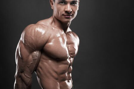 Strong bodybuilder with six pack. Athlete man with perfect abs, shoulders,biceps, triceps and chest, personal fitness trainer flexing his muscles