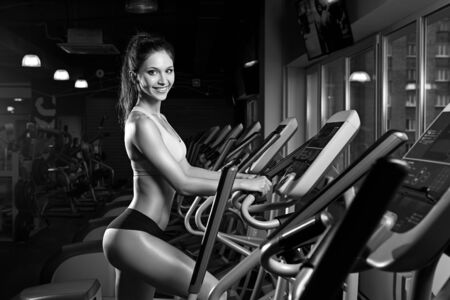 elliptic: Beauty girl workout exercise on elliptic bike. Young, beautiful woman training by riding a bicycle in a gym. Concept of healtly lifestyle and sport. Stock Photo