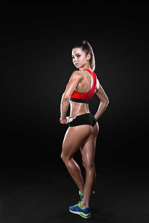showing muscles: Athletic young woman showing muscles of the back and hands on a isolated black background