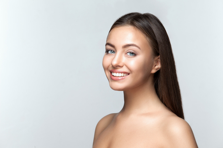 beautiful teeth: Portrait of attractive caucasian smiling woman brunette on gray background, studio shot toothy smile face long hair head and shoulders Stock Photo