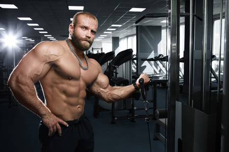 latissimus: Muscular athletic bodybuilder fitness model posing after exercises in gym
