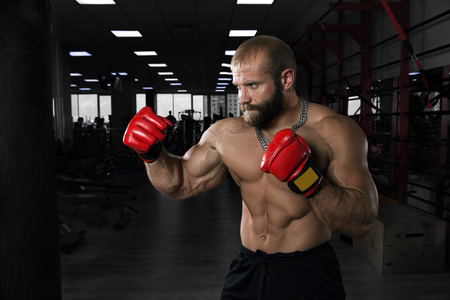beat the competition: Strong muscular man training in the gym. Athlete with boxing gloves has a punching bag.