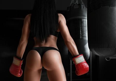 夢のお尻。セクシーなスポーティな女性の彼女の完璧なお尻を披露して手袋を身に着けているボクシングのポーズのショットをトリミング