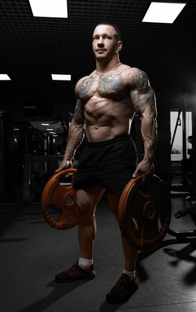 latissimus: Muscular athletic bodybuilder model posing after exercises in gym Stock Photo
