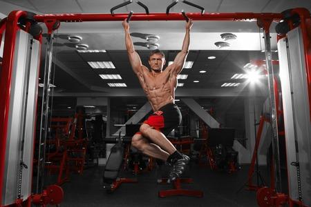 and the horizontal man: Muscular shirtless man doing pulling up on horizontal bar. Stock Photo