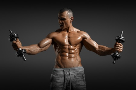 Muscular athletic bodybuilder model posing after exercises in gym Stock Photo