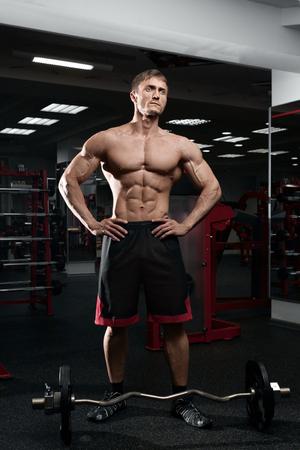 retouched: Muscular athletic bodybuilder model posing after exercises in gym Stock Photo