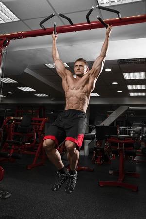 Muscular shirtless man doing pulling up on horizontal bar. Stock Photo