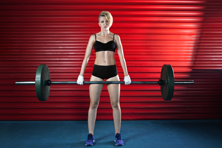 heavy weight: Muscular woman in a gym doing heavy weight exercises Stock Photo
