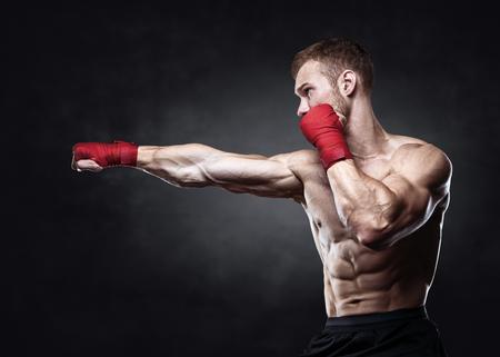 Muscular kickbox o muay thai peighter punching.