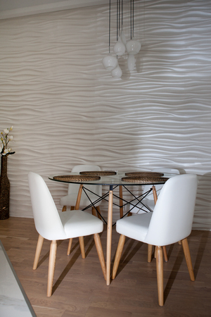 dining table and chairs: A round table and white chairs and background.