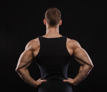 Portrait of a muscular male model against black background. Personal trainer. Black t-shirt. Back view.