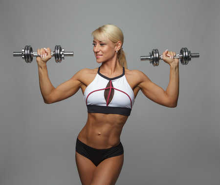 Athletic beautiful woman doing exercise for arms