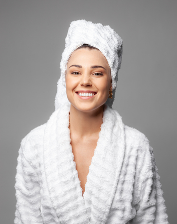 Attractive girl wearing white towel on head and white bath robe, smiling Foto de archivo