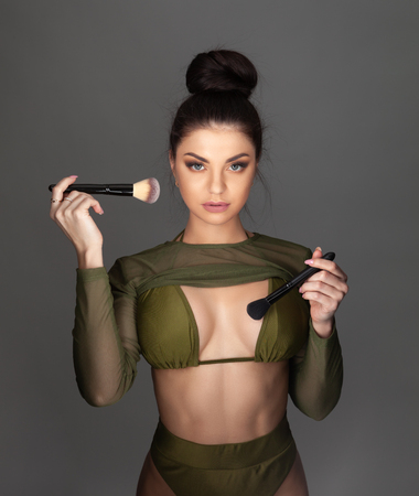 Young beautiful brunette woman holding makeup brushes. Reklamní fotografie