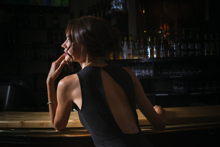 elegant lady in black dress, in restaurant at a bar Stock Photo