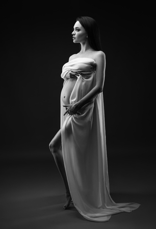 Beauty and sexy of young pregnant woman with white material - grey background