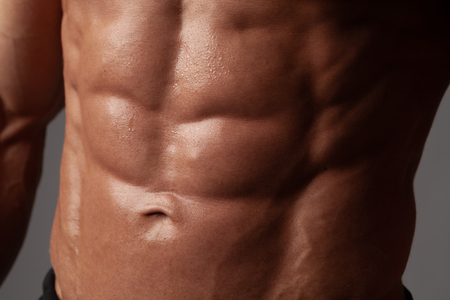 Male abdominal muscles closeup with sweat drops after exercise