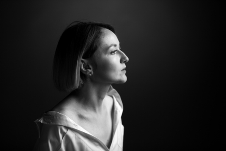 Dramatic black and white portrait of a beautiful woman on a dark background