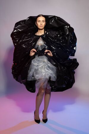Girl posing in a dress made of plastic film. Fashion portrait. The concept of using artificial materials in clothing, environmental pollution with polyethylene products. Reklamní fotografie