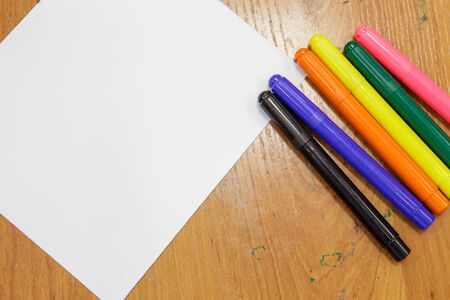A set of colored markers and a sheet of white paper on the table. 스톡 콘텐츠 - 132047882