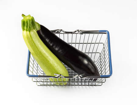 Eggplant and zucchini in the shopping basket. Shopping concept with fresh vegetables on white background.