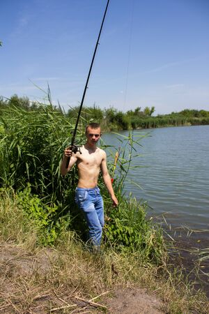 catch wrestling: man with a fishing rod pulling water from the lake Stock Photo