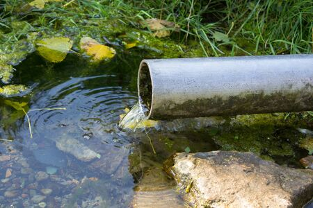 sanctified: water pipes spring, clean water spring flows from a pipe Stock Photo