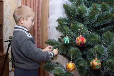 decorates: boy decorates Christmas tree balls green toys