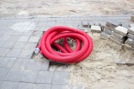 sewer pipe: corrugated sewer pipe with twisted red lying on the pavement