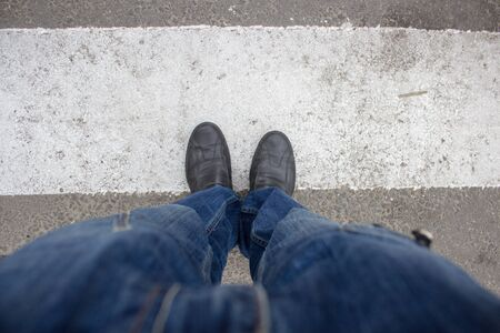 men s feet: standing at pedestrian crossing person view from above