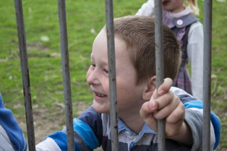 despite: boy looks through a metal fence and smiling