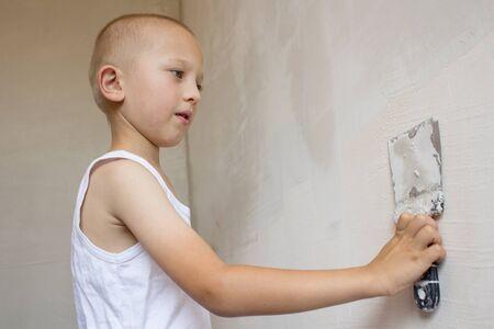 skim: man hand with trowel plastering a wall, skim coating plaster walls Stock Photo