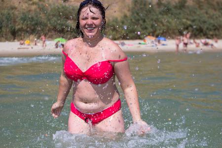 donna in mare giocando con l'acqua che spruzza in gocce d'acqua