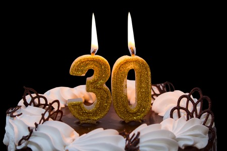 White frosted cake with 30 lit candles. 30th birthday cake