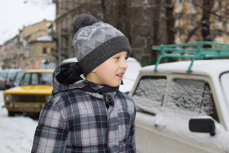 boy and car in the winter after snowfall Stock Photo