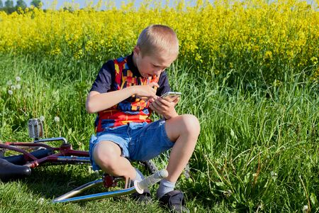 boy in nature flips through the COVID-19 epidemic and disease news website Zdjęcie Seryjne