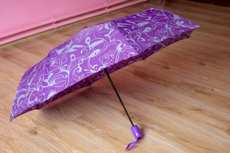 purple umbrella opened in a room on the floor Фото со стока