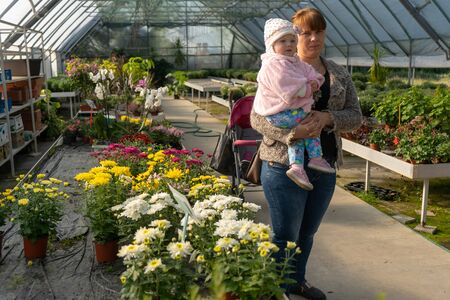 Mom and her baby in a plant shop,mom with a girl in her arms in a flower shop