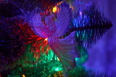 Christmas angel at night hanging on a Christmas tree glowing in colorful garlands