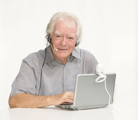 netbooks: Old man with netbook, headset and webcam Stock Photo