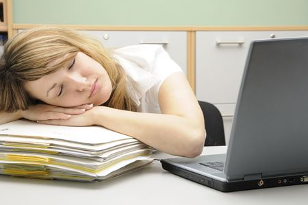 Young woman in an office, sleeping photo
