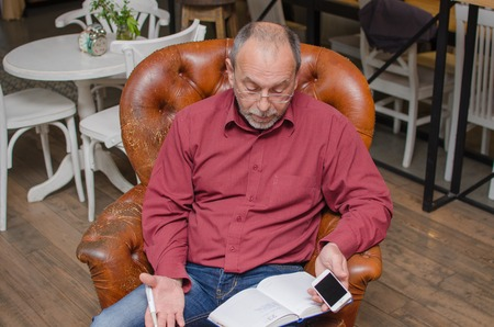 clothes organizer: Aged man with day planner uses cellphone
