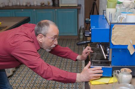 Aged man making coffee on the coffe machine