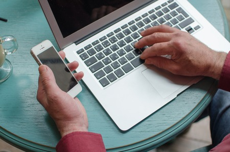 lap top: Aged man using his phone and lap top in the cafe Stock Photo