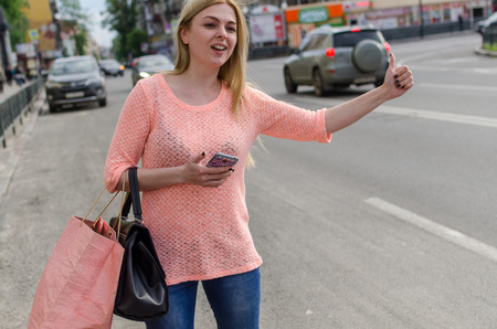 catching: Young blonde woman is catching taxi on the street Stock Photo