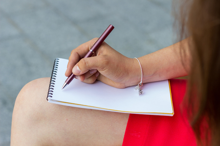 clothes organizer: Young woman making notes in the note book onthe street